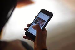 Mulheres como uma foto na aplica??o de Instagram no smartphone fotos de stock
