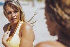 Mulheres consideravelmente desportivos que falam na praia foto de stock