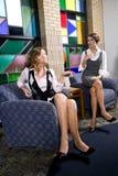 Mulheres consideravelmente novas que sentam-se na cadeira da sala de espera foto de stock royalty free