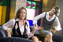 Mulheres consideravelmente novas que sentam-se na cadeira da sala de espera Fotografia de Stock Royalty Free