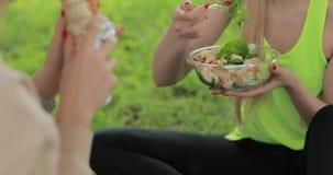 Mulheres da aptid?o que comem a salada fresca em um parque, alimento saud?vel do vegetariano video estoque