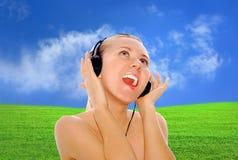 Mulheres da felicidade com nos auscultadores no céu azul fotografia de stock