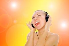 Mulheres da felicidade nos auscultadores e na música de escuta fotografia de stock