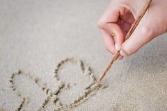 Mulheres das mãos que escrevem na areia e no volume de água foto de stock