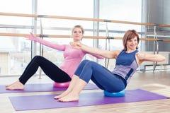 Mulheres de ajuda do instrutor pessoal de Pilates da ginástica aeróbica Fotos de Stock Royalty Free