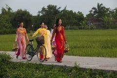 Mulheres de Christian Vietnamese que vestem Ao Dai ao andar à igreja em uma estrada secundária imagens de stock