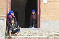 Mulheres de Hani que descansam na frente de uma casa local fotografia de stock