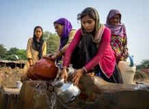 Mulheres de Mumbai que enchem potenciômetros da água fotografia de stock