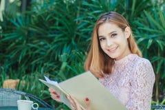 Mulheres de negócio asiáticas trabalho de sorriso e escrita de um livro e de um che fotos de stock royalty free
