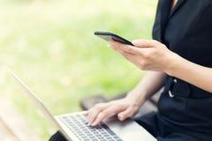 Mulheres de negócio que usam o portátil e o smartphone ao trabalho fotografia de stock royalty free