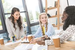 mulheres de negócios alegres multiculturais com o café a ir ter a conversação imagem de stock
