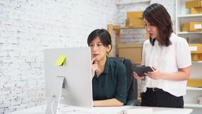 Mulheres de negócios asiáticas que usam a tabuleta no escritório video estoque