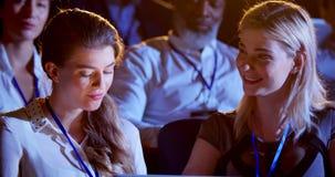 Mulheres de negócios caucasianos que trabalham no portátil durante o seminário no auditório 4k filme