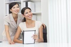 Mulheres de negócios chinesas & latino-americanos asiáticas que usam o computador da tabuleta Imagens de Stock Royalty Free