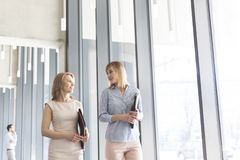 Mulheres de negócios com arquivos que falam ao andar no corredor pelo escritório fotografia de stock royalty free