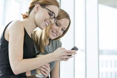 Mulheres de negócios de sorriso que usam o telefone celular durante a ruptura no escritório fotos de stock