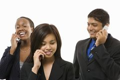 Mulheres de negócios e homem de negócios que falam em telefones de pilha. Imagens de Stock Royalty Free