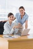 Mulheres de negócios felizes na mesa que sorriem na câmera Imagens de Stock Royalty Free