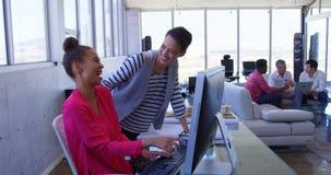 Mulheres de negócios multi-étnicas bonitas que discutem sobre o computador pessoal no escritório moderno 4k video estoque