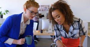 Mulheres de negócios multi-étnicas bonitas que discutem sobre o portátil no escritório moderno 4k vídeos de arquivo