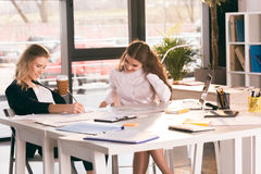 Mulheres de negócios novas de Siling que trabalham junto na tabela com portátil Fotos de Stock