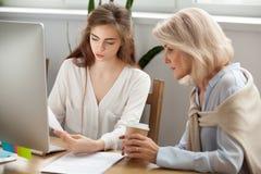 Mulheres de negócios novas e mais idosas que discutem os originais que trabalham o toget foto de stock