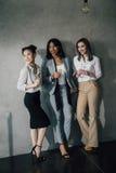 Mulheres de negócios novas que estão junto com vidros do champanhe e que olham afastado Fotos de Stock
