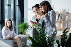 Mulheres de negócios novas que estão junto e que usam o smartphone com o colega que senta-se atrás Foto de Stock