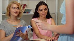 Mulheres de negócios novas que falam em uma reunião