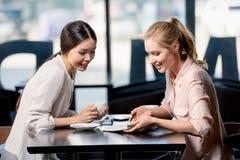 Mulheres de negócios novas que olham o caderno e que discutem o projeto na ruptura de café imagens de stock