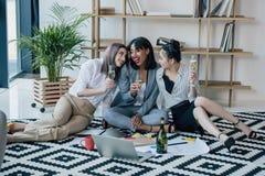 Mulheres de negócios novas que sentam-se no tapete com portátil e champanhe bebendo Foto de Stock