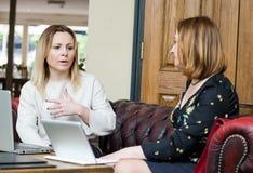 Mulheres de negócios novas que têm a conversação na reunião informal fotografia de stock