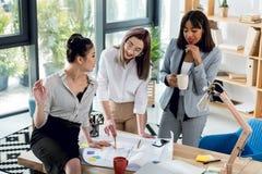 Mulheres de negócios novas que trabalham com modelo e café bebendo no escritório Imagens de Stock Royalty Free