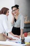 Mulheres de negócios novas que trabalham com modelo e que discutem o projeto novo Imagem de Stock