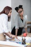 Mulheres de negócios novas que trabalham com modelo e que discutem o projeto novo Foto de Stock