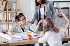 Mulheres de negócios novas que trabalham com modelos e que discutem o projeto novo Imagem de Stock
