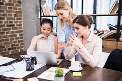 Mulheres de negócios novas que trabalham junto na mesa com portátil e que discutem Imagens de Stock