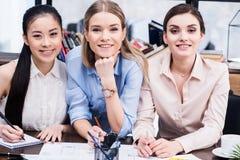 Mulheres de negócios novas que trabalham junto na tabela e que sorriem na câmera Imagens de Stock