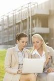 Mulheres de negócios novas que usam o portátil junto ao sentar-se contra o prédio de escritórios Fotografia de Stock Royalty Free
