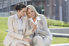 Mulheres de negócios novas que usam o telefone celular junto ao sentar-se contra o prédio de escritórios Fotografia de Stock