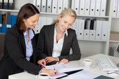 Mulheres de negócios novas seguras que sentam-se na mesa de escritório Fotografia de Stock Royalty Free