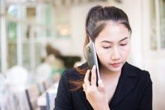 Mulheres de negócios que consultam o sócio pelo telefone ao sentar-se na cafetaria imagem de stock