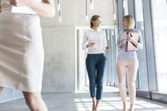 Mulheres de negócios que discutem ao andar no corredor no escritório fotos de stock royalty free