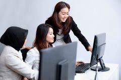 Mulheres de negócios que dizem a informação a seu colega de trabalho foto de stock royalty free