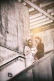 Mulheres de negócios que estão na escadaria e que usam a tabuleta Imagens de Stock Royalty Free