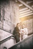 Mulheres de negócios que estão na escadaria e que usam a tabuleta digital Foto de Stock Royalty Free