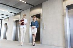 Mulheres de negócios que falam ao andar para fora do elevador na entrada do escritório fotografia de stock