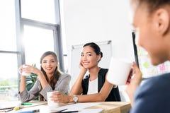 Mulheres de negócios que falam e que bebem o café Foto de Stock