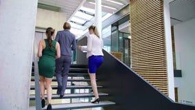 Mulheres de negócios que interagem um com o otro ao andar em escadas filme