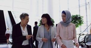 Mulheres de negócios que interagem um com o otro na entrada no escritório 4k vídeos de arquivo